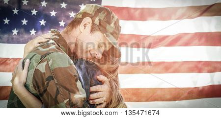 American soldier embracing his partner in front of american flag while reuniting