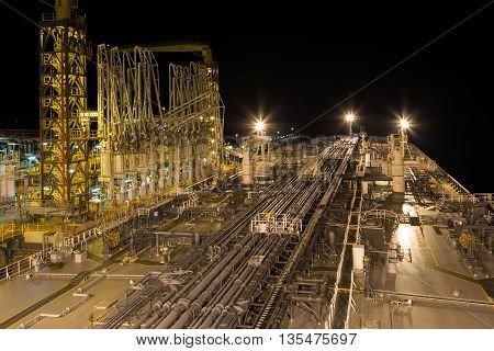 Oil transfer terminal with moored to the berth tanker at night.
