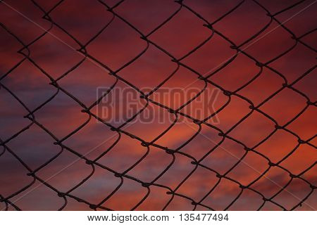 Tragic sky with fiery red clouds on grating.