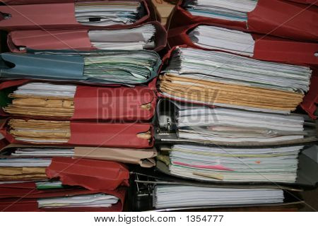 Twin stacks of untidy files of old legal papers poster