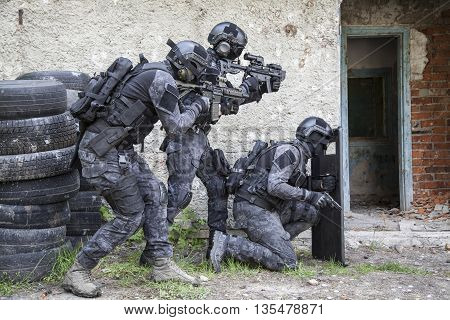 Spec ops police officers SWAT in black uniform in action