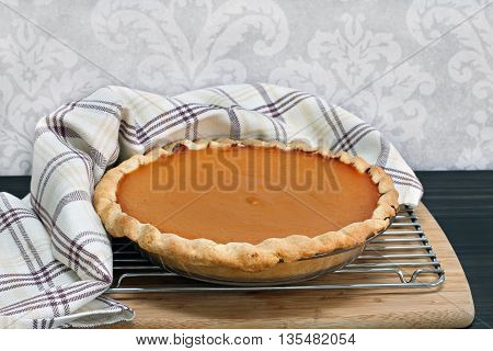 Homemade pumpkin pie cooling with towel wrap.