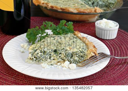 Spinach and feta cheese pie slice with whole pie in background.