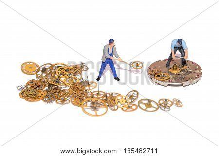 Miniature people repairing clockwork. Teamwork. Help in the work. Working employees. A pile of gear. Gears and clockwork isolated.