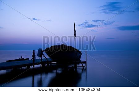 Docked boat a the cottage at dusk