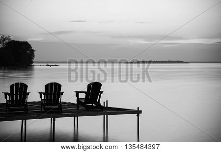 Three cottage chairs in a row on a dock at the cottage at dusk