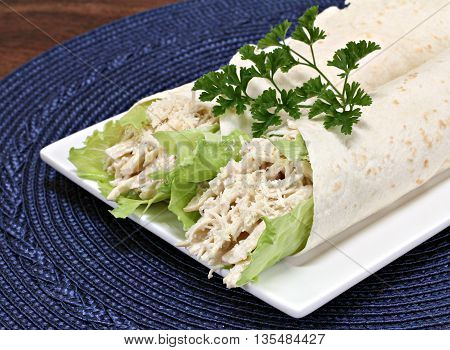 Two chicken caesar wraps with shredded chicken lettuce and parmesan cheese garnished with parsley. Close up partial view.