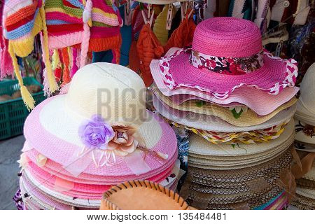 Array of pink and white hats on display at roadside store