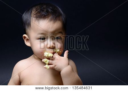 Cute asian baby eating cake with his hand