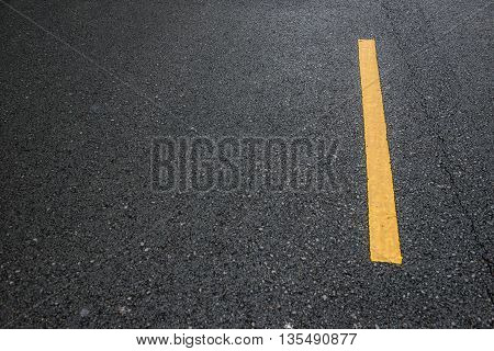 blacktop with a yellow line in day time