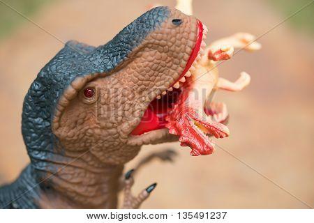 gigantic tyrannosaurus bites a smaller dinosaur close up