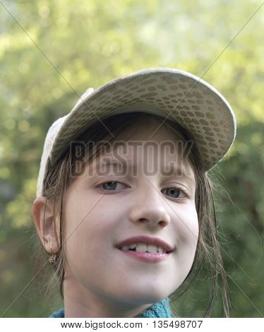 Happy girl with a curious look on her face vertical outdoor portrait with particular focus