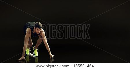 Composite image of sportsman waiting on the starting block against a black background