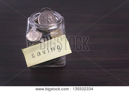 Finacial concept. Money in the glass on wooden table with Saving word and copy space area.