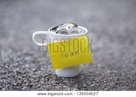 Coins in mug with load label blurred at background. Financial concept.