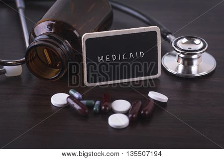 Stethoscope pill bottle Various pills capsules and MEDICAID on wooden background with copyspace area.