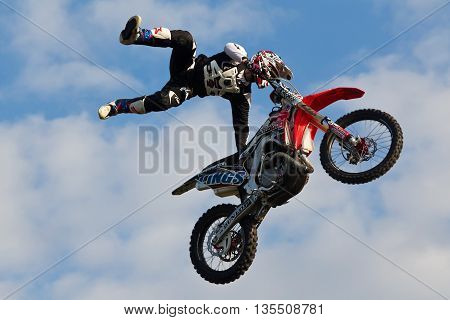 NEWBURY, UK - SEPTEMBER 21: An FMX stunt rider completes a mid air off the bike manoeuvre for the watching crowd at the Berks County show on September 21, 2014 in Newbury