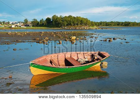 Fishing boat in the shallows during evening low tide