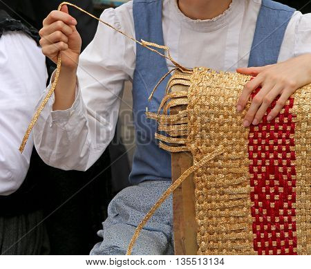 Young Girl Creates Patiently A Straw Bag In The Street