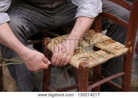 Mender Of Chairs While Repairing A Old  Wooden Chair