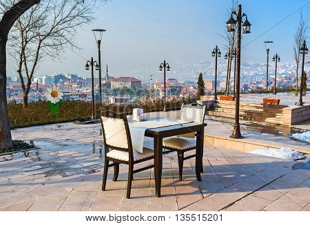 The outdoor restaurant on the Castle Hill overlooks the lower town with the Haci Bayram Mosque on adjacent hill Ankara Turkey.