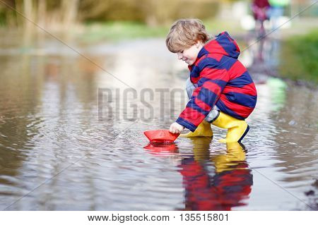 Funny little kid boy in rain boots playing with paper ship by a puddle on warm spring day. Active leisure for children. Child having fun outdoors.