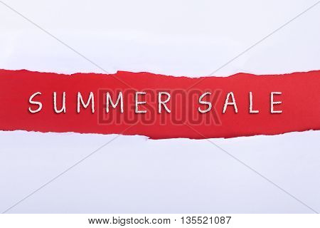Torn paper with a SUMMER SALE word on red background.