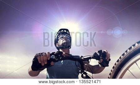 Composite image of man cycling with mountain bike against sunlight