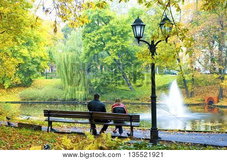 Autumn. The young man and the girl on a bench in park