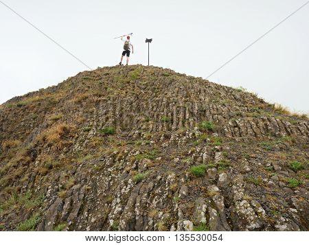 Tourist On Sharp Basalt  Peak Of Volcano  Formation