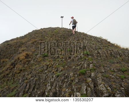 Hiker Climbing On Sharp Peak Of Basalt Formation Of Volcano