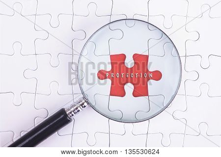 Business Concept - Magnifier Glass on white puzze with PROTECTION Word