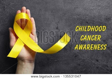 Hand holding yellow ribbon and text Childhood Cancer Awareness on dark background