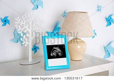 Lamp and photo frame with ultrasound scan of baby on shelf in children room