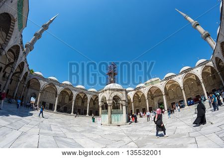 ISTANBUL TURKEY - JUNE 20 2015: People visiting Sultan Ahmet Mosque in Istanbul Turkey. The mosque is popularly known as the Blue Mosque for the blue tiles adorning the walls of its interior