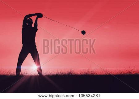 Front view of sportsman practicing hammer throw against red sky over grass