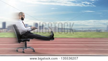 Fast business - businessman sitting with laptop runs on track