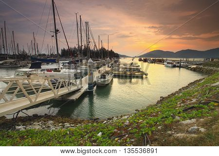 Beautiful composition view of Malaysian Harbour with a yatch during sunset. Noise slighty appear and soft focus due to long exposure