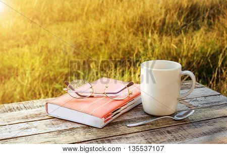 Cup of coffee and note book on wooden table background with morning sunlight
