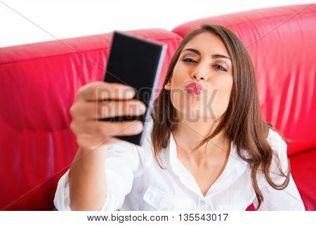 High angle view of young woman taking selfie. Beautiful female is puckering while holding smart phone. She is sitting on red sofa over white background.