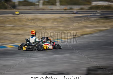 Karting - driver in helmet driving on kart circuit