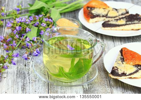 Glass of sage herbal tea with cake. Decorated with flowering sage lat. Salvia officinalis