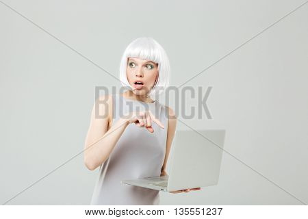 Unconfident pretty young woman holding and using laptop over white background