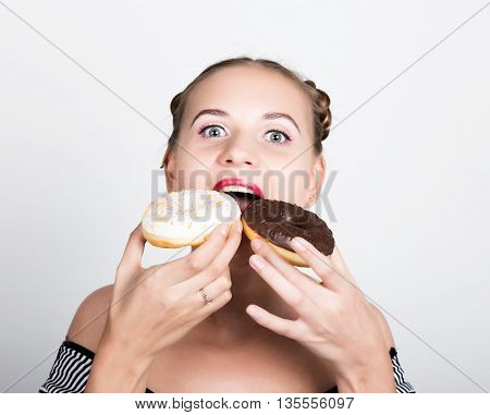 girl in bright makeup eating a tasty donut with icing. Funny joyful woman with sweets, dessert. dieting concept. junk food.