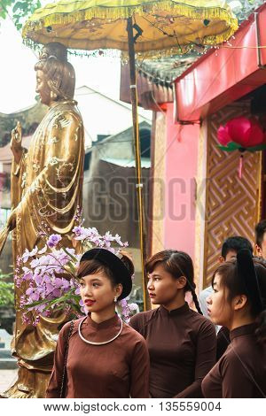 Thanh Hoa, Vietnam - October 19, 2014: Vietnamese girls dressed in Ao Dai, the traditional Vietnamese dress, stand in front of a statue of Guanyin, the spiritual figure of mercy, in front of a temple before attending a spirit mediumship ceremony in Centra