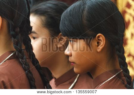 Thanh Hoa, Vietnam - October 19, 2014: Young Vietnamese girls dressed in Ao Dai, the traditional Vietnamese dress, and silver necklaces before a spirit mediumship ceremony at a temple in Central Vietnam.