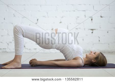 Pregnant Young Woman Doing Prenatal Yoga. Bridge Pose