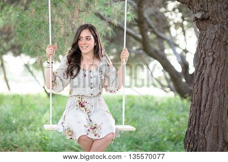 Smiling Woman Sitting on a Swing in a Park