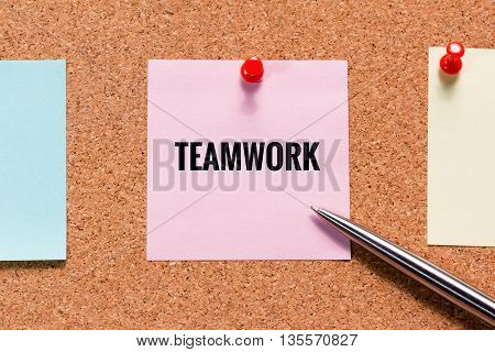 Pink sticky note on cork board with teamwork word and push red pin concept
