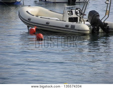 Single inflatable dinghy with outboard motor lies at anchor in a harbor . Tuscany Italy